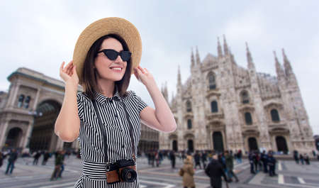 portrait of young beautiful woman tourist in straw hat with camera over Duomo cathedral in Milan, Italy Banco de Imagens