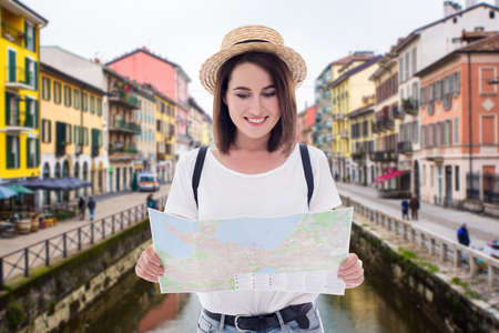 portrait of young beautiful woman tourist walking with map in old italian town