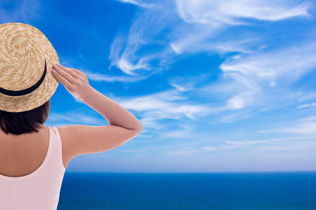 summer vacation and travel concept - back view of young woman in swimsuit and straw hat and copy space over blue sky background
