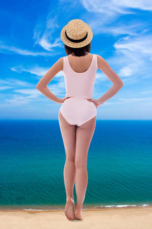 summer vacation and travel concept - back view of giant young woman in pink swimsuit and straw hat standing on sea coast