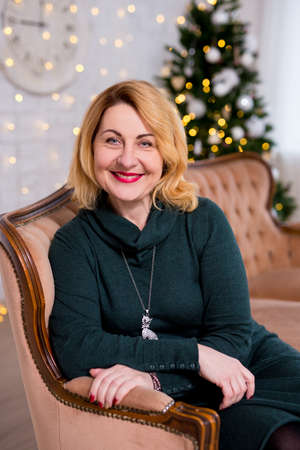 portrait of happy mature woman sitting near decorated christmas tree Imagens