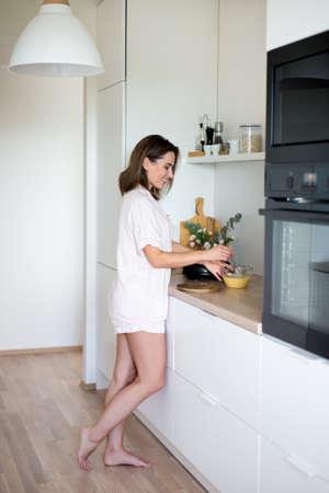 Atractiva mujer joven en pijama cocinando el desayuno en la cocina moderna