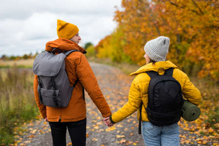 rear view of couple hikers with backpacks walking in autumn forest Reklamní fotografie