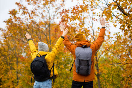 back view of cheerful couple hikers with backpacks in autumn forest