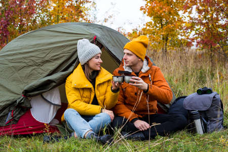 travel, trekking and hiking concept - couple of hikers drinking tea or coffee near green tent in beautiful autumn forest