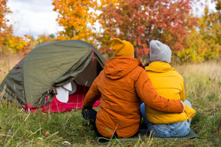 travel, love and autumn concept - back view of cute couple in love sitting near green tent in autumn forest
