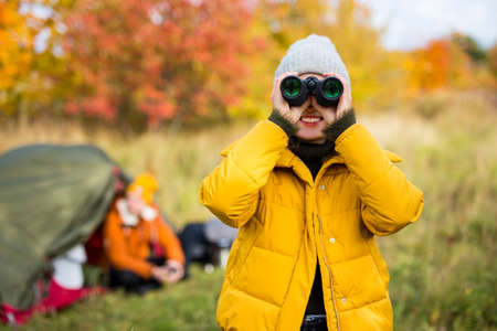 travel, trekking and hiking concept - young beautiful woman with binoculars posing near green tent in autumn forest Reklamní fotografie