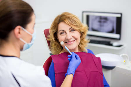 portrait of cheerful mature woman in dentist office with doctor