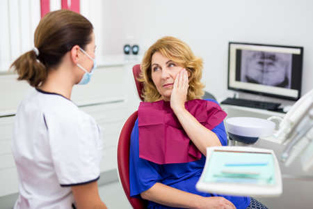 portrait of attractive mature woman with pain in dentist office with doctor Imagens