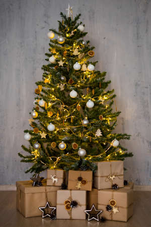 christmas tree and heap of gifts over concrete wall background