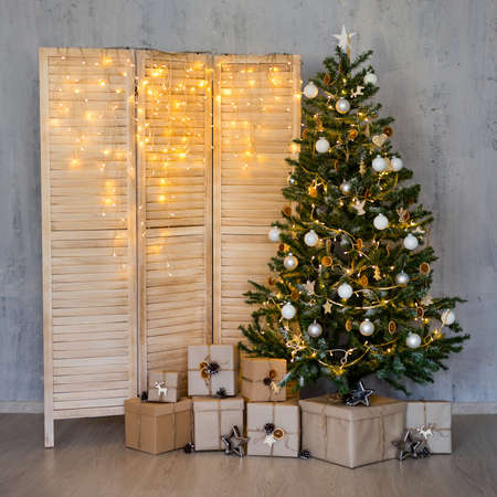 Christmas background - christmas tree, heap of gifts and folding screen with garland lights