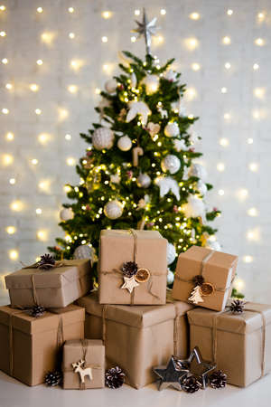 christmas and new year background - heap of beige gift boxes near decorated christmas tree with lights Stok Fotoğraf