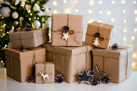 christmas background - close up of beige gift boxes near decorated christmas tree