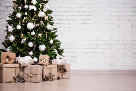 decorated christmas tree and gift boxes over white brick wall background with copy space