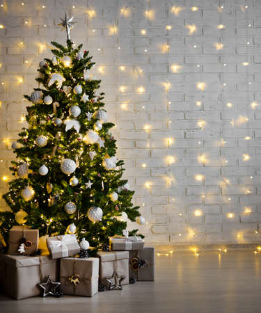 decorated christmas tree with white balls, garlands and gift boxes over white brick wall - copy space
