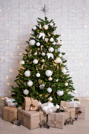 decorated christmas tree and heap of gift boxes over brick wall background