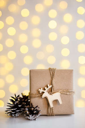 close up of gift box and fir cones over shiny yellow garland lights background with copy space