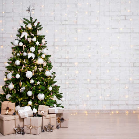 decorated christmas tree, heap of gift boxes and copy space over white brick wall background