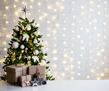 christmas and new year concept - beige gift boxes near decorated christmas tree and copy space over white brick wall with lights 写真素材