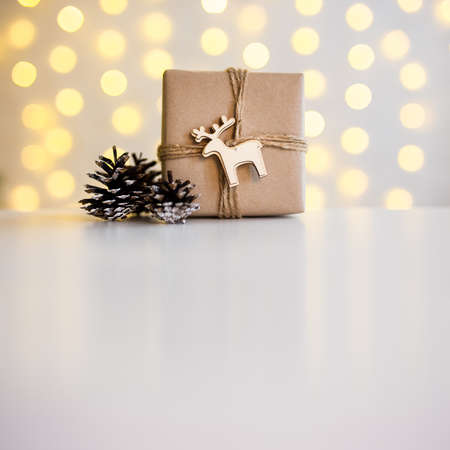 close up of gift box and fir cones over yellow lights and white table background with copy space Stok Fotoğraf