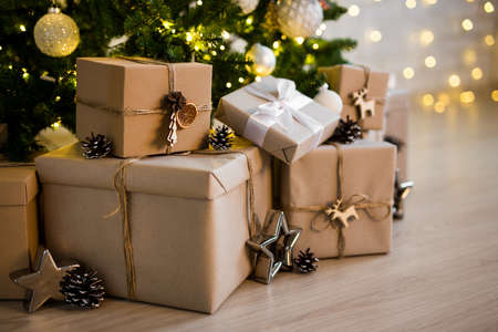 close up of beige gift boxes near decorated christmas tree at home