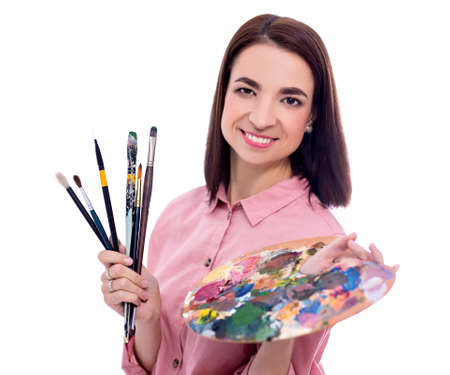 portrait of young beautiful woman artist with palette and paint brush isolated on white background Фото со стока