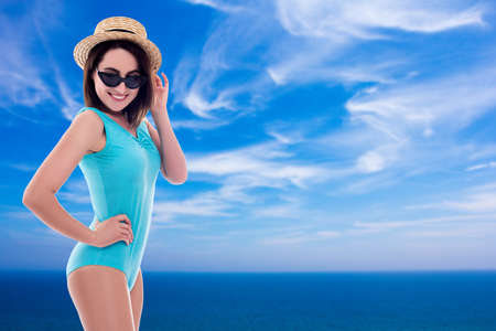 summer and travel concept - young beautiful woman in swimsuit posing at the beach - copy space over blue sky and clouds