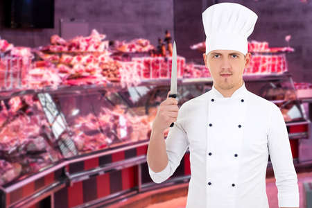 portrait of handsome male butcher, shopkeeper or cook posing with big knife in the market Фото со стока - 132488138
