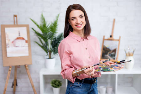 portrait of young woman artist posing with palette and paint brush at home or studio Фото со стока