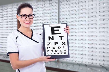 young woman optometrist or consultant holding clipboard with eyevision test chart at optics store