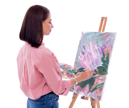 back view of young woman artist with easel, palette and paint brush painting picture isolated on white background