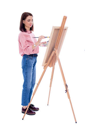 full length portrait of young woman artist with easel, palette and paint brush painting picture isolated on white background