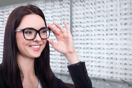 eyesight and vision concept - happy young woman choosing glasses at optics store
