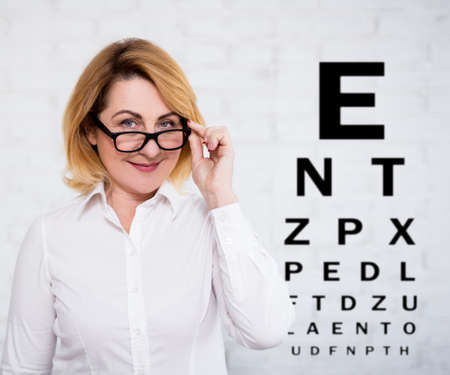 portrait of cheerful mature business woman in eyeglasses and eyevision test chart over white wall background