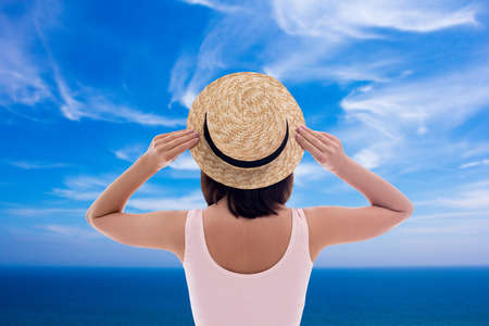 summer vacation and travel concept - back view of young woman in swimsuit and straw hat over blue cloudy sky background