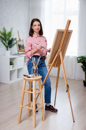 full length portrait of young beautiful woman artist painting at home or in studio