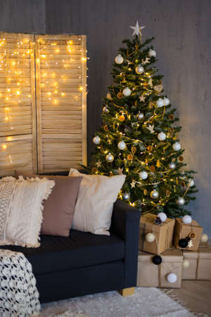 Christmas background - decorated living room with Christmas tree, gift boxes, sofa and folding screen with garland lights