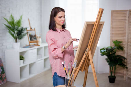 young beautiful woman artist painting at home or in studio