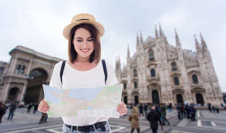 portrait of young beautiful woman tourist with map walking in Milan, Italy