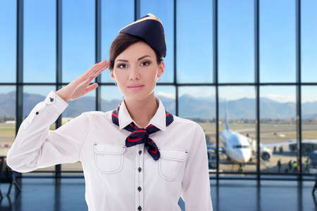 summer, vacation and travel concept - young stewardess posing in modern airport