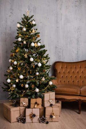 christmas tree, heap of gifts and vintage sofa over grey concrete wall background