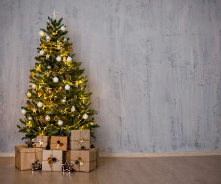 christmas tree and heap of gifts - copy space over concrete wall background