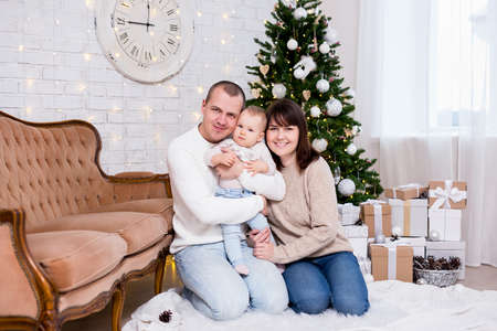 christmas and family concept - portrait of young family with cute little baby girl daughter near decorated christmas tree