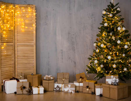 Christmas and new year evening background - christmas tree, gifts, folding screen with lights and copy space over grey concrete wall Фото со стока - 132676359