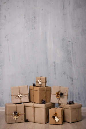 heap of gift boxes and copy space over grey concrete wall background