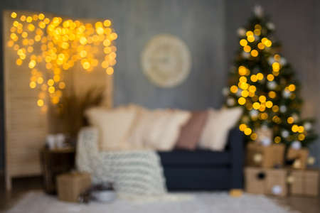 Christmas background - blurred living room with decorated Christmas tree, gifts and garlands