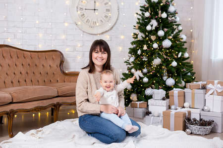 christmas and family concept - portrait of happy young mother and cute little baby girl daughter near decorated christmas tree Фото со стока