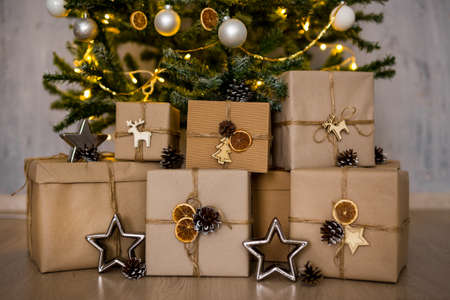 close up of decorated gift boxes under christmas tree over concrete wall background Фото со стока