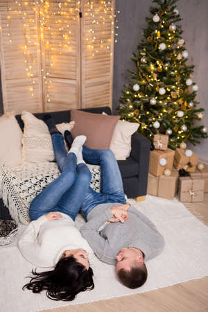 christmas, new year and love concept - young couple in love relaxing in decorated living room with Christmas tree and gift boxes Фото со стока