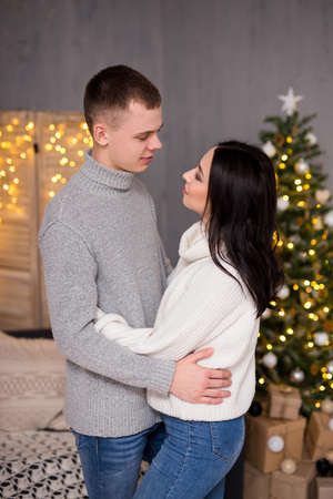 christmas, new year and love concept - cute couple in love posing over Christmas background with garlands